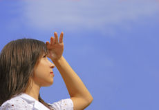 Future expectations. Young woman looking with interest in the distance over a blue cloudy sky.Useful image for designs connected with ideas of future,success Royalty Free Stock Images