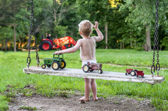 Young child waving and playing. Little boy playing with tractors on an old wooden swing, and waving to his daddy who is in the background on a tractor Royalty Free Stock Photos