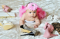 Future fashion model. Fashion  baby girl laying on the bed with high heels shoes and bags Stock Photo