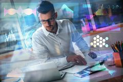 Future and finance concept. Businessman working on project at workplace with digital business hologram. Future and finance concept. Double exposure Royalty Free Stock Photo