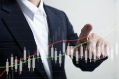Businessman touching increasing graph. Future of financial business concept,Businessman touching increasing graph with finance symbols coming Royalty Free Stock Images