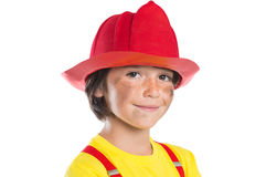 Future firefighter. Closeup face of smiling boy wearing firefighter helmet isolated on white background. Happy cute boy smiling and looking at camera with his Stock Images