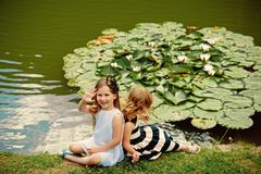 Future and flourishing. Children happy smile on green lake landscape. Germination and growth. Summer vacation concept. Girl wave hand at pond with water lily stock images