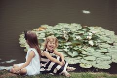 Future and flourishing. Children happy smile on green lake landscape. Summer vacation concept. Girls sit on grass at pond with water lily flowers. Germination royalty free stock photography