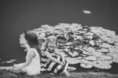 Future and flourishing. Children happy smile on green lake landscape. Summer vacation concept. Girls sit on grass at pond with water lily flowers. Germination stock images