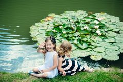 Future and flourishing. Children happy smile on green lake landscape. Germination and growth. Summer vacation concept. Girl wave hand at pond with water lily stock photo