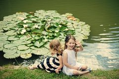 Future and flourishing. Children happy smile on green lake landscape. Germination and growth. Summer vacation concept. Girl wave hand at pond with water lily royalty free stock images