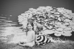 Future and flourishing. Children happy smile on green lake landscape. Germination and growth. Summer vacation concept. Girl wave hand at pond with water lily royalty free stock photo
