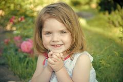 Future and flourishing. Girl smiling with folded hands in summer garden. Child sitting at blossoming rose flowers on green grass. Innocence, purity and youth stock photo