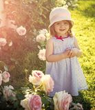 Future and flourishing. Girl in hat with folded hands in summer garden. Innocence, purity and youth concept. Child smiling at blossoming rose flowers on green stock photography