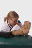 Future Generation Doctor. Little blond girl playing dress up as a doctor examining her teddy bear royalty free stock photography