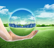 Future green energy. Hands holding a crystal ball with wind turbines and solar panels royalty free stock photo
