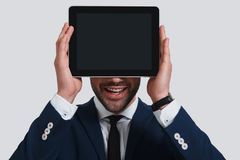 Future is here. Happy young man in full suit covering face with. Digital tablet and smiling while standing against grey background Royalty Free Stock Photo