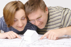Future house dreams. Young couples looking closely at building plan with white little cardboard house model Stock Image
