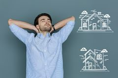 Ambitious student thinking about buying a house. Future house. Young student closing his eyes and dreaming about buying a big beautiful house Stock Image