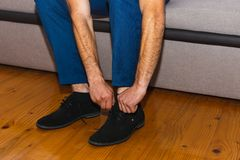 A future husband tightens up for a wedding by putting on his shoes and tying his ties royalty free stock images