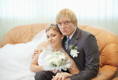 Future husband and wife on leather sofa Royalty Free Stock Photo