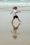 Future kid. A beautiful girl child walking in the sand on the beach on a misty morning Royalty Free Stock Photography