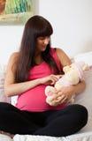 Future mère avec l'ours de nounours Photos stock