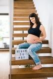 Future mère de beau bébé lissant le ventre et souriant dans la nouvelle maison Photo stock