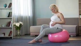 Future mère heureuse appréciant la grossesse, doucement frottant le ventre, attendant le bébé images stock