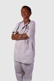 Future male nurse. Young mixed race black ethnic boy wearing white scrubs uniform with stethoscope stock image