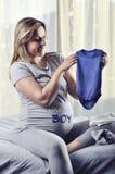 Future maman heureuse montrant le costume à venir de bébé garçon Photos stock