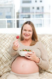 Future mom with a bowl of strawberries Stock Image