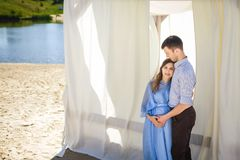 Future mother and father hugging near alcove on beach. Future mother with curly long hair in beautiful blue dress and handsome father hugging near light alcove Royalty Free Stock Photography