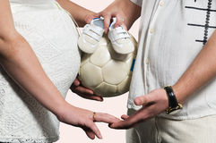 Future mother and father holding hands. Man holds hand of a pregnant woman and soccer ball with small baby shoes Stock Photos