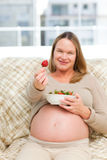 Future mother showing a strawberry to the camera Stock Photos