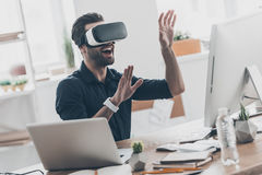 Future is now. Handsome young man in VR headset gesturing and smiling while sitting in creative office Royalty Free Stock Photography