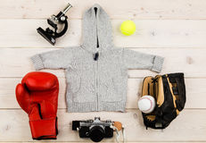 Future occupation concept. Top view of grey baby boy hoodie surrounded with boxing glove, baseball equipment, tennis ball, microscope and photo camera on light Royalty Free Stock Photos