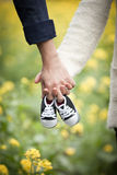Future parents holding hands and a pair of little shoes stock photography