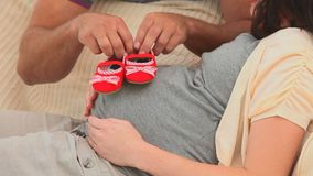 Future parents holding little red shoes Stock Photos