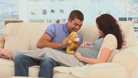 Future parents playing with a teddy bear stock video footage