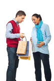Future parents at  shopping. Man showing to his pregnant wife  inside of shopping bags and the woman being surprised and happy  isolated on white background Stock Photography