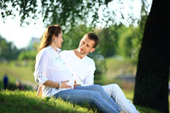 Future parents sitting on the grass in the Park on a Sunny day. Stock Images