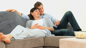Future parents watching tv Royalty Free Stock Images