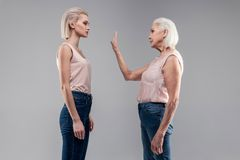 Old grey-haired woman with bob haircut showing stopping gesture. Future and past. Old grey-haired women with bob haircut showing stopping gesture to serious good stock photography