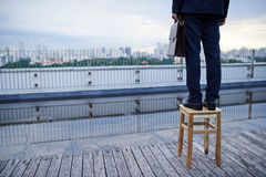 Future prospects. Businessman standing on the stool to be able to see the cityscape stock images