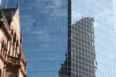 Future reflection. Picture of an old building in front of a newer glass office building, with a third building reflected on the modern one royalty free stock photos