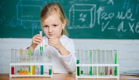 Future scientist. Explore and investigate. School lesson. Interesting approach to learn. Girl cute school pupil play. With test tubes and colorful liquids royalty free stock photography
