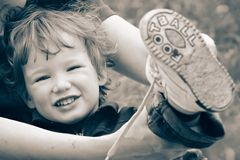 Future soccer player. Mum dresses boots to the little boy after game in football on beach sand Stock Photos