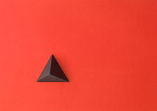 Future space. Red paper tetrahedron on red paper. Copy space available. Usefull for business cards and web Royalty Free Stock Photos