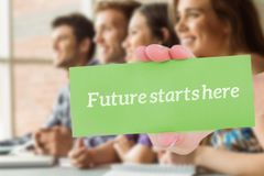 Future starts here against smiling friends students talking and writing. The word future starts here and hand showing card against smiling friends students Stock Photo