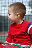 Future of tennis. Adorable little boy sitting next to the tennis net with a racjet in his hands Stock Image