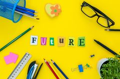 Future - text of carved letters at yellow table background with office or pupil supplies.  Royalty Free Stock Photo