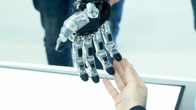 Future today. A man touches the hand of a robot. The robotic arm rotates, touches the human arm. Modern technology