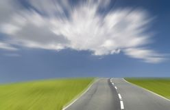 The future under a blue sky. On a highway through the grass plains stock photo